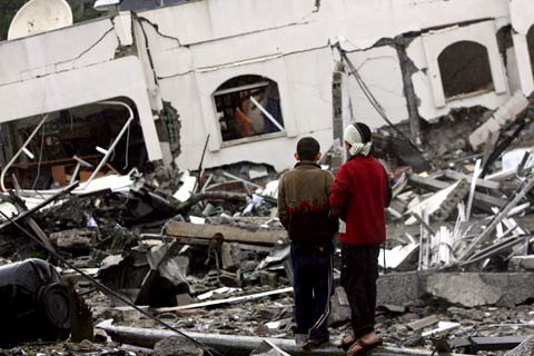 Rapazes palestinianos olham o que resta das instalações do primeiro-ministro do Hamas. Foto LUSA/EPA