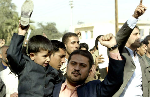 Iraquiano exibe sapato durante manifestação em Basra, sul do Iraque, pela libertação do jornalista preso por atirar os sapatos contra Bush. Foto EPA/HAIDER AL-ASSADEE