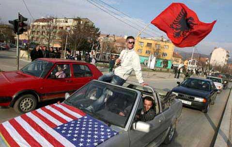 Manifestantes acenam bandeira albanesa e norte-americana em comemoração à proclamação da independência do Kosovo, em Mitrovica, Kosovo. Foto Lusa/EPA/VALDRIN XHEMAJ