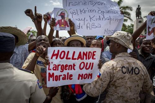"""A frase """"Hollande, dinheiro, sim, moralidade, não"""" podia ser lida nos cartazes, quando visitou o Haiti em maio de 2015"""