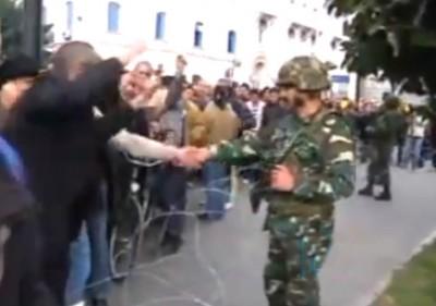 Manifestante cumprimenta soldado esta sexta-feira em Tunis.
