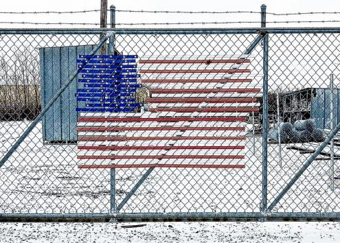 Bandeira americana numa vedação de arame farpado. Foto de Glen Zazove/Flickr.