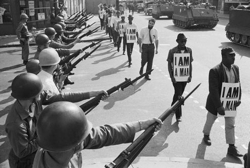 """Memphis, 1968. A Guarda Nacional bloqueia uma rua enquanto os manifestantes negros trazem um cartaz a dizer """"eu sou um homem"""". Foto de bswise/Flickr."""
