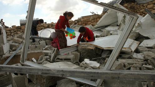 Crianças palestinianas no meio de ruínas