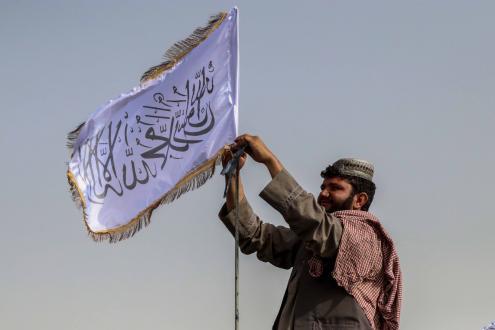 Combatente talibã ergue a sua bandeira num veículo em Kandahar. Foto de STRINGER/EPA/Lusa.