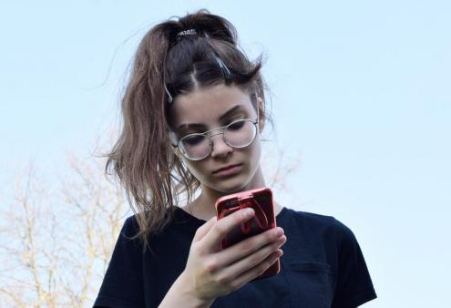 Adolescente olha para o telemóvel.