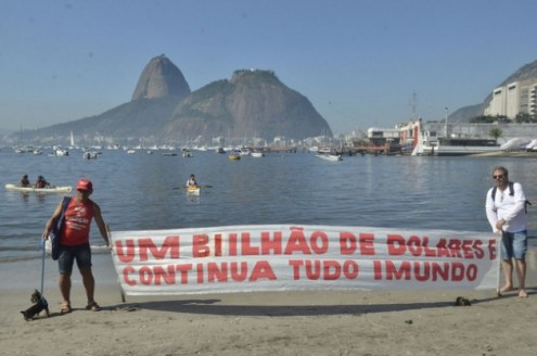 """""""Um bilhão de dólares e tudo continua imundo"""", diz uma faixa na praia da baía de Guanabara, no Rio de Janeiro, onde acontecerão várias competições náuticas dos Jogos Olímpicos e cuja descontaminação é uma promessa não cumprida. Foto: Fernando Frazão/Agência Brasil"""