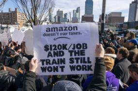 """Protesto da população contra a instalação da sede da Amazon em Queens, """"a Amazon não paga impostos"""" lê-se na faixa"""