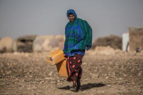 Mulher africana carrega bidões de água. Foto da Oxfam no Twitter.