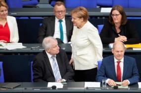 Angela Merkel, Horst Seehofer e Olaf Scholz, ministro das Finanças, no parlamento alemão, 3 de julho de 2018 - Foto de Hayoung Jeon/Epa/Lusa