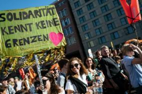 """""""Solidariedade não conhece fronteiras"""" pode ler-se no cartaz de uma participante na manifestação realizada neste sábado em Berlim – Foto de Kamil Zihnioglu/Epa/Lusa"""