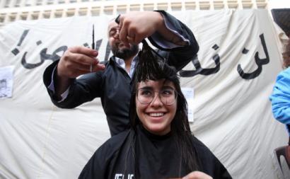 Manifestante libanesa numa ação simbólica de corte de cabelo em frente ao Banco Central.
