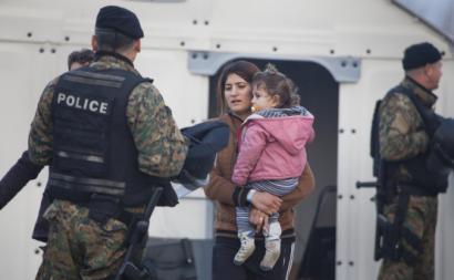 Mulher refugiada com criança abordada pela polícia local.
