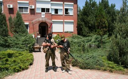 Dois soldados do Batalhão Azov em frente ao edifício de uma das bases do movimento em Uzuf. Atrás de si há uma suástica.