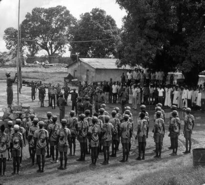 Hastear da bandeira da Guiné Bissau após o arrear da de Portugal em Canjadude. Foto (original a cores) de João Carvalho, Wikimedia - domínio público.