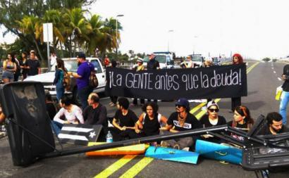 """Protesto com faixa """"La gente antes que la deuda"""", Porto Rico"""