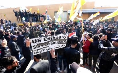 Manifestantes ostentam a placa de entrada da Embaixada dos EUA no Iraque. Janeiro de 2020.