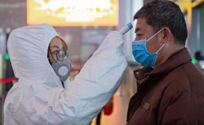 Equipas médicas tiram a temperatura aos passageiros na estação ferroviária de Nanjing, China.