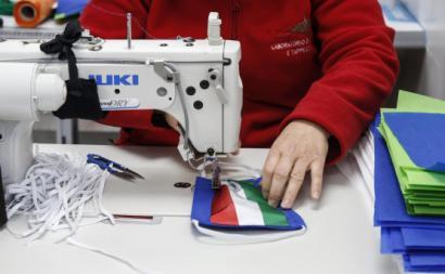 Trabalhadora italiana costura máscara de proteção. Abril de 2020. Foto de FABIO FRUSTACI/EPA/LUSA.