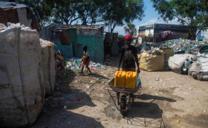 No meio do surto de coranvírus, uma habitante do campo de La Piste carrega contentores de água. Este acampamento foi criado na sequência do terramoto de 2010. Os seus habitantes têm de se deslocar cerca de dois quilómetros para terem acesso a água potável. Port-au-Prince, Haiti, abril de 2020. Foto de ean Marc Herve Abelard/EPA/LUSA.