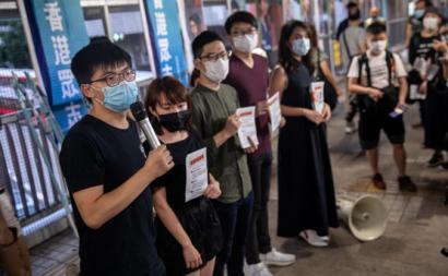 Membros do partido Demosisto distribuem panfletos contra a nova Lei de Segurança Nacional chinesa esta sexta-feira. Foto de Jerome Favre/EPA/Lusa.