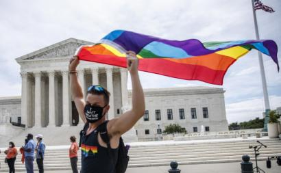 Homem celebra a decisão do Supremo Tribunal dos EUA com bandeira arco-íris à porta desta instituição. Foto de SHAWN THEW/EPA/Lusa.