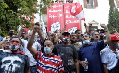 """Manifestantes libaneses em frente a duas faixas de que dizem """"Beirute Capital da Revolução"""" e """"Beirute Capital sem armas"""". Agosto de 2020. Foto de WAEL HAMZEH/EPA/Lusa."""