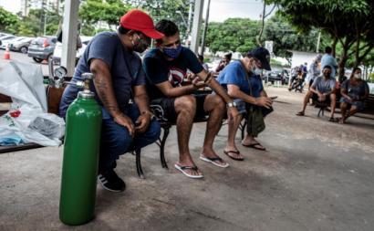 Um habitante de Manaus com uma garrafa de oxigénio que comprou para a sua mãe hospitalizada. Foto de Raphael Alves/EPA/Lusa.