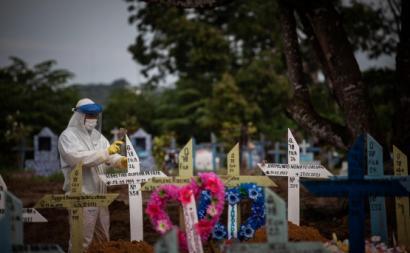 Trabalhador coloca cruzes nas campas de pessoas falecidas devido à pandemia em Manaus. Foto de RAPHAEL ALVES/EPA/Lusa.
