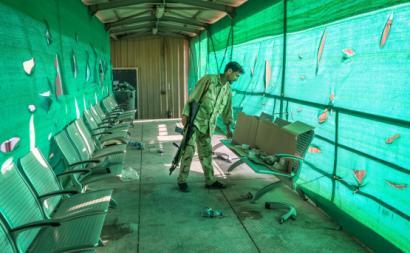 Soldado afegão analisa o que o exército dos EUA deixou para trás na base de Bagram, o seu principal reduto militar no Afeganistão. Foto de HEDAYATULLAH AMID/EPA/Lusa.