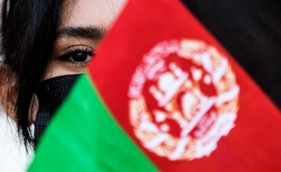 mulher por detrás de bandeira do Afeganistão