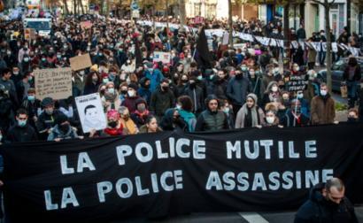"""Manifestação em Paris contra a lei de """"segurança global"""", faixa com a palavra de ordem """"Polícia mutila, Polícia Mata"""" - Foto de  Christophe Petit Tesson/Epa/Lusa"""