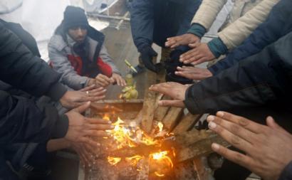Migrantes aquecem-se numa fogueira durante um dia de inverno no campo de refugiados de Lipa nos arredores de Bihac, Bósnia e Herzegovina, a 1 de janeiro de 2021.