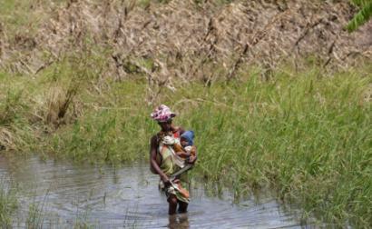 Mulher com criança na única via de acesso possível na zona de João Segredo onde a estrada nacional 6 foi interrompida pelo ciclone Idai na província de Sofala, centro de Moçambique, 23 de março de 2019. Foto de Tiago Petinga/Lusa