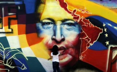 Criança junto a mural em Caracas que lembra Chávez - foto CLAE/estrategia.la