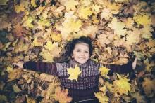 Criança a brincar com folhas secas.