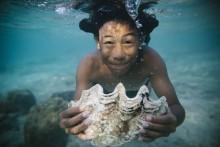 Jovem segura concha debaixo de água.