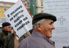 """Idoso com cartaz a dizer """"2 milhões de portugueses vivem na pobreza""""."""