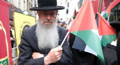 Homem judeu com uma bandeira palestiniana numa manifestação. Foto de Alisdare Hickson/Flickr.