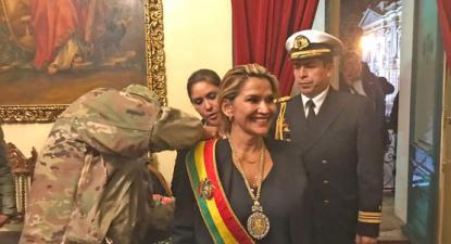 Jeanine Añez, auto-proclamada presidente da Bolívia, recebe a faixa presidencial das mãos dos militares.