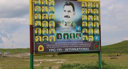 """Cartaz no Curdistão sírio em que se pode ver o líder do PKK, Abdullah Öcalan ladeado por mártires combatentes, as siglas das unidades curdas da síria (YPG e YPJ) e a frase: """"Os nossos mártires são a nossa honra"""". Neste cartaz a Turquia é classificada como fascista. Fotografia: José Manuel Rosendo/Abril 2019"""