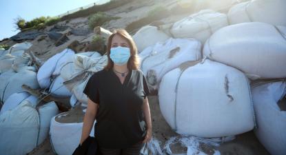 """Catarina Martins junto à """"parede de sacos de plástico"""" na Praia da Estela na Póvoa de Varzim, 26 de julho de 2021 - Foto de Estela Silva/Lusa"""