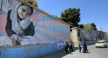 Vendedor ambulante expõe bandeiras e posters dos líderes talibãs junto a um mural de uma menina na escola.