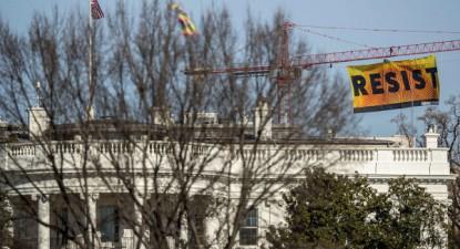 """""""Resiste"""", apelo escrito numa bandeira colocada por ativistas da Greenpeace num guindaste de construção perto da Casa Branca, Washington em 25 de janeiro de 2017 – Foto da Greenpeace"""