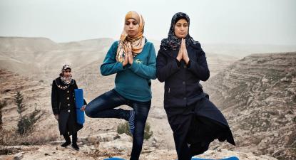 Hayat (à esquerda) ensina yoga às residentes da sua aldeia, Zataara, nos arredores de Bethelehem, na Cisjordânia. Foto de Tanya Habjouqa/ Panos Pictures.