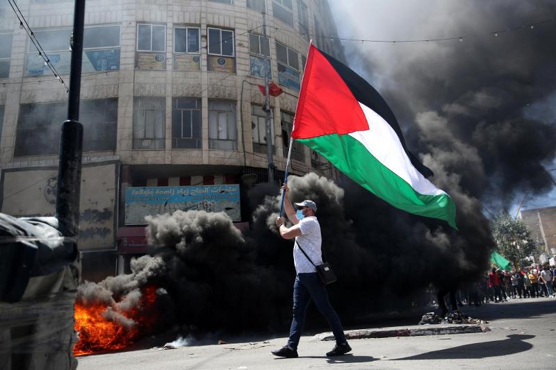 """""""o adiamento das eleições e a escalada de violência de Israel contra Palestinianos, seja dentro da Faixa de Gaza, na Cisjordânia ou em Jerusalém Oriental, leva a que a sociedade civil Palestiniana se encontre uma vez mais, impossibilitada de fazer-se ouvir"""" - Manifestante palestiniano em Hebron. Foto de Abed Al Hashlamoun/EPA/Lusa."""